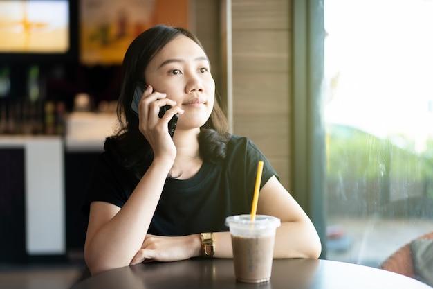 コーヒーショップやレストラン、よそ見女性に座って美しい幸せなアジア女 Premium写真