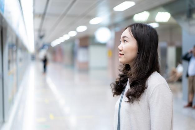 Красивая азиатская женщина ждет поезд в метро (подземная) платформа Premium Фотографии