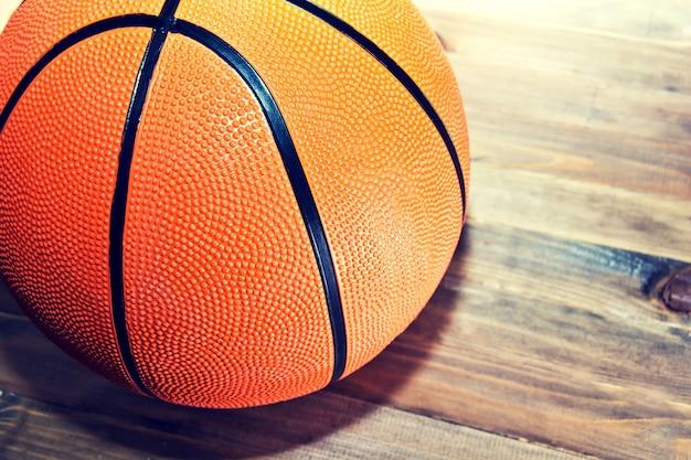 木製のハードウッドフロアにバスケットボールボール。 無料写真
