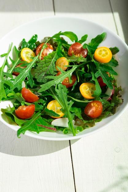 キンカンとトマトチェリーの新鮮なルッコラのサラダ Premium写真