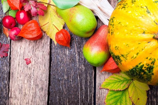 素朴な木製のテーブルに秋の果物とひょうたんの感謝祭。 Premium写真