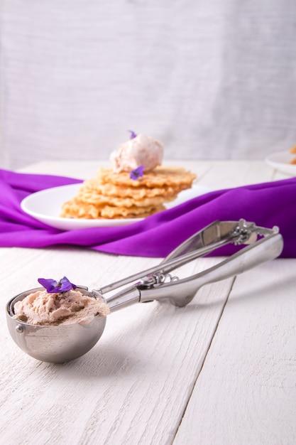 Ложка с мороженым, бельгийская вафля на белой тарелке, украшенная фиолетовым цветком, Premium Фотографии