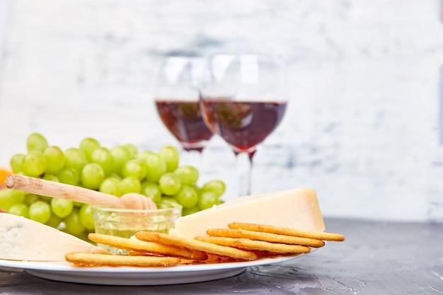 Сырная тарелка и вино в бокалах Premium Фотографии