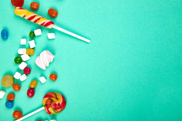 Разноцветные конфеты на пастельных бирюзовых. плоская планировка Premium Фотографии