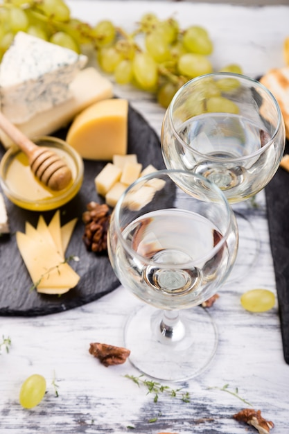チーズプレート。クルミとチーズの品揃え、石のスレートプレートに蜂蜜をパンします。 Premium写真