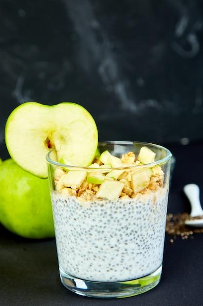 Здоровый чиа пудинг с яблоками и мюсли в стекле. Premium Фотографии