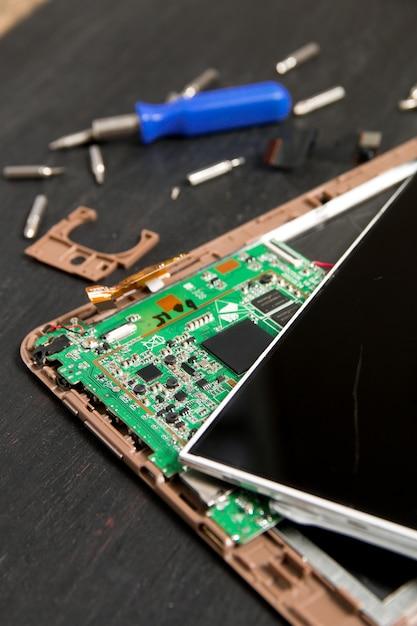 Процесс ремонта планшетного пк рядом с отверткой и бит на черном фоне деревянные. Premium Фотографии