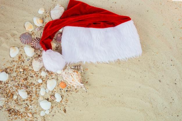 Рождественская шляпа на пляже. санта шляпа на песке возле снарядов. Premium Фотографии