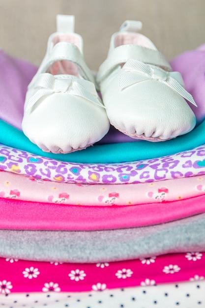 Сложить розовый и белый комбинезон с туфлями на нем на сером фоне деревянных. Premium Фотографии