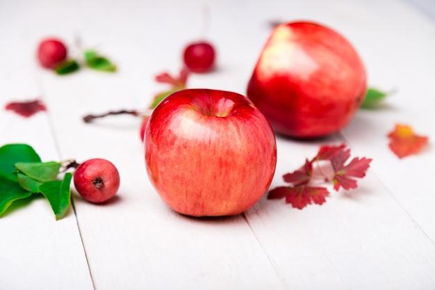 白い木製の大小の赤いリンゴ。閉じる。秋。 Premium写真