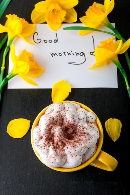Кружка кофе с желтым нарциссом цветы и цитаты доброе утро на черном столе. день матери или женский день. поздравительная открытка вид сверху. завтрак. Premium Фотографии