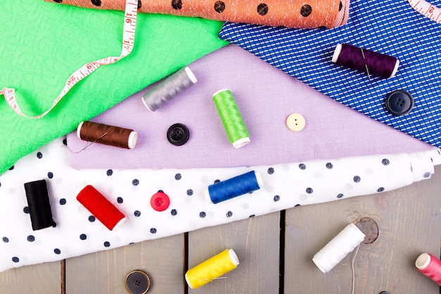 服を縫うためのアイテム。縫製ボタン、糸と布のスプール。上面図。 Premium写真