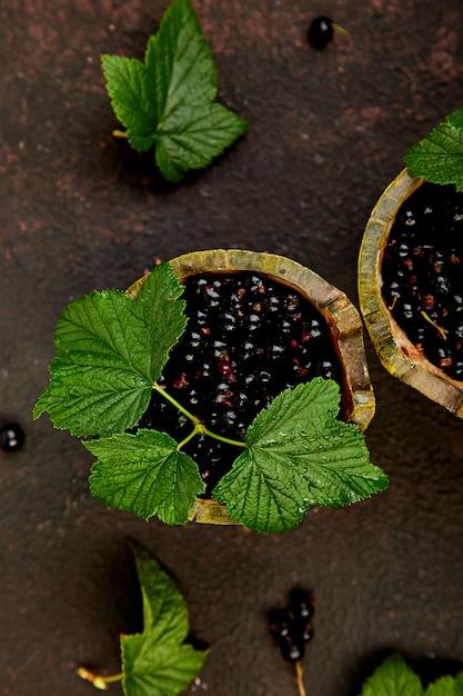 ブラックカラントの果実、葉、緑のボウルに黒スグリ。 Premium写真