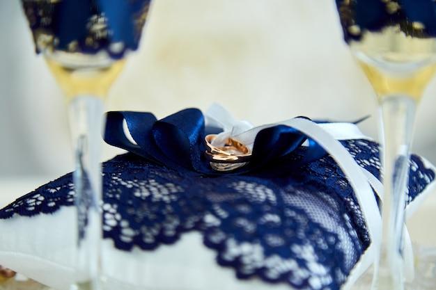 Два бокала шампанского и подушка с обручальными кольцами Premium Фотографии