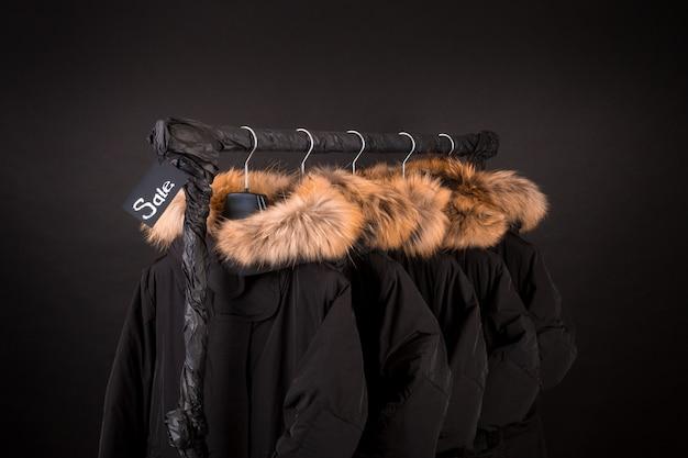 たくさんの黒いコート、フードラックに掛かっているフード付きのジャケット。 Premium写真