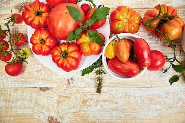 トマトの背景のミックス。美しいジューシーな有機赤いトマト Premium写真