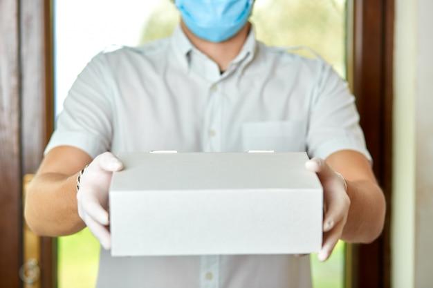 宅配便、医療用ラテックス手袋とマスクの配達員がコロナウイルスの流行中にドアに白い箱でオンライン購入を安全に配達します Premium写真