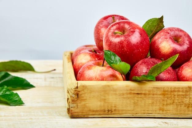 Свежие красные спелые яблоки фрукты в деревянной коробке Premium Фотографии