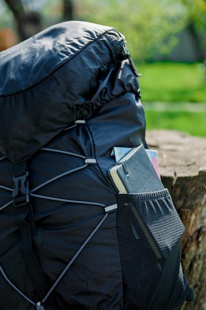 Черный рюкзак с блокнотом, картой и карандашом Premium Фотографии