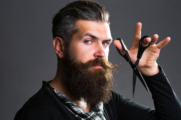 長いひげ口ひげを持つ若いハンサムなひげを生やした男 Premium写真