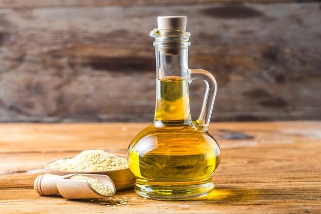 ゴマ種子、古い木製のテーブルに油を入れたボトル、ガラスジャグのゴマ油。 無料写真