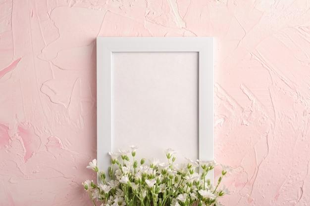 ピンクの織り目加工のテーブル、トップビューコピースペースにマウス耳ハコベの花と白い空のフォトフレーム Premium写真