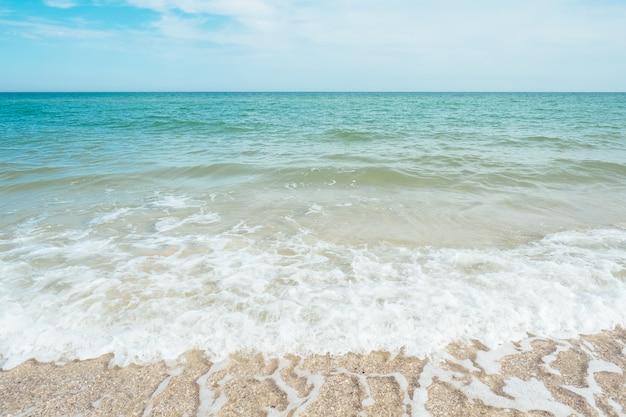 Синие бирюзовые морские волны с облаками песка и неба Premium Фотографии