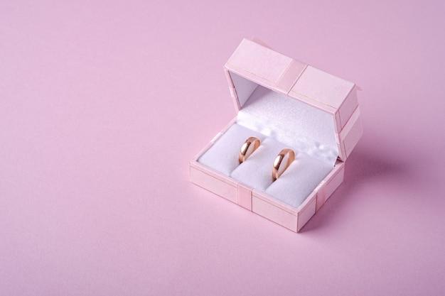 Обручальные золотые кольца в розовой подарочной коробке на нежно-розовом фоне, угол обзора, копия пространства Premium Фотографии