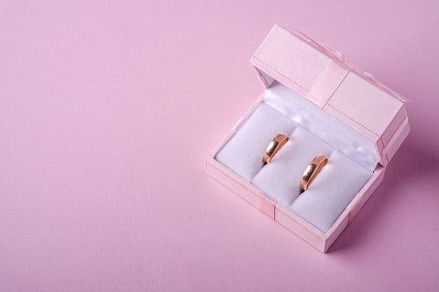 柔らかいピンクの背景、視野角、コピースペースにピンクのギフトボックスに結婚式の金の指輪 Premium写真