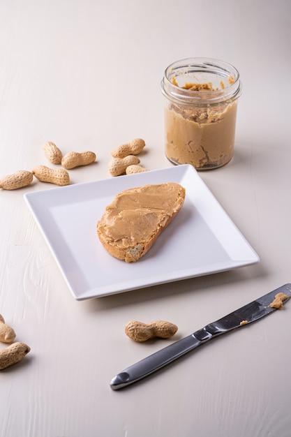 白い正方形プレートピーナッツナットテーブルナイフにピーナッツバターパンサンドイッチ Premium写真