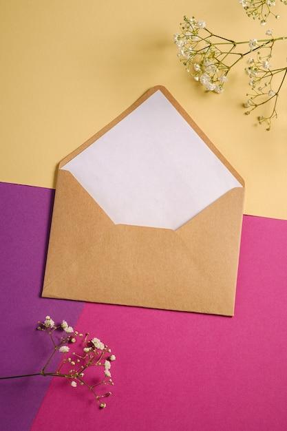 Конверт из крафт-бумаги с белой пустой карточкой и цветами гипсофилы Premium Фотографии