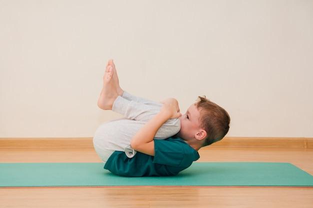 Милый маленький мальчик учится заниматься йогой в тренажерном зале Premium Фотографии
