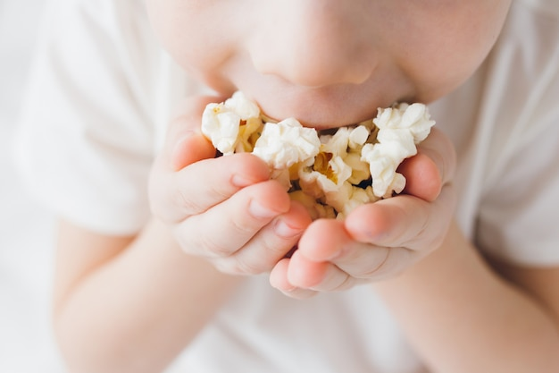白いリネンが付いているベッドに座っているポップコーンを食べるかわいい男の子 Premium写真