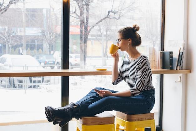 スマートフォンで音楽を聴くとコーヒーを飲む女の子 Premium写真