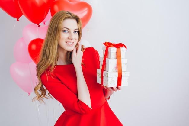 赤いドレスの女の子はギフトボックスを保持します Premium写真