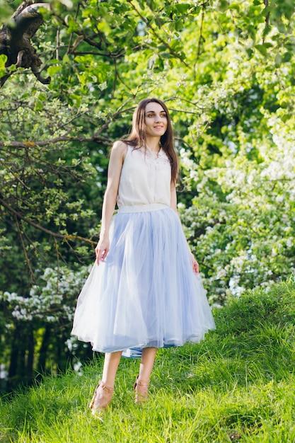 Молодая женщина стоит на холме на фоне цветущих деревьев Premium Фотографии