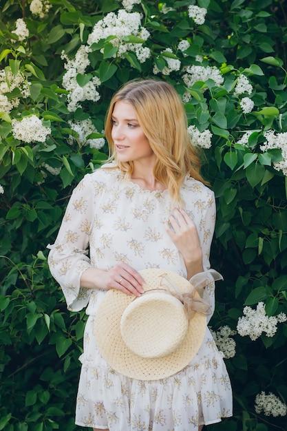春にライラックの花を持つ金髪の女性 Premium写真