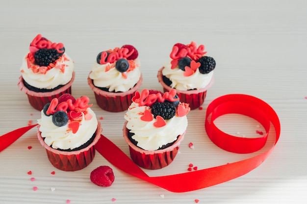Кексы с белыми сливками, свежими ягодами и украшением Premium Фотографии