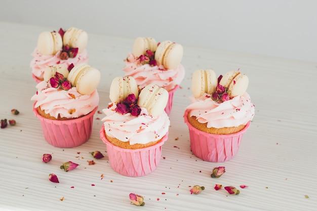 Кексы с розовым кремом, миндальное печенье и розы Premium Фотографии