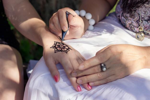 Мастер менди рисует хну на женской руке Premium Фотографии