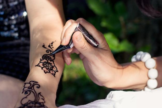 マスター一時的な刺青は、女性の手にヘナを描きます Premium写真