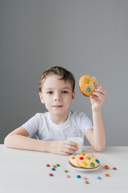 子供は自家製のビスケットと牛乳を食べて幸せです Premium写真