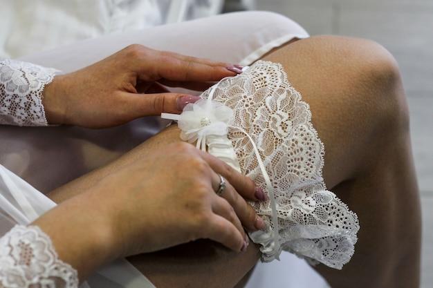 ブライダルガウンは素敵な白いレースの結婚式のガーターです。花嫁を集める Premium写真