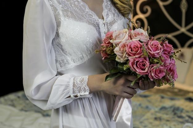 集まる花嫁の手にピンクのバラのウェディングブーケ Premium写真