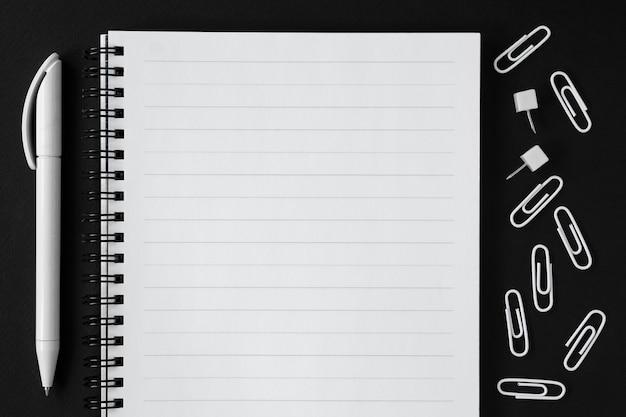 リストとペンを黒の背景に行います。学校に戻る。 Premium写真