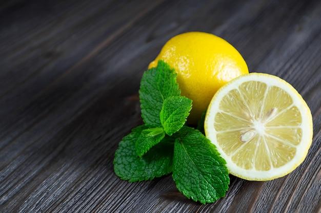 新鮮なレモンとミントの葉の暗い木製のテーブル。 Premium写真