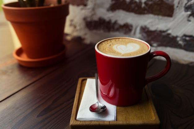Капучино в красной кружке на деревянном столе Premium Фотографии