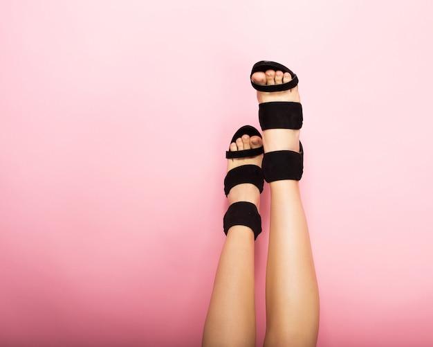 ピンクの背景に黒いハイヒールの女性の足 Premium写真
