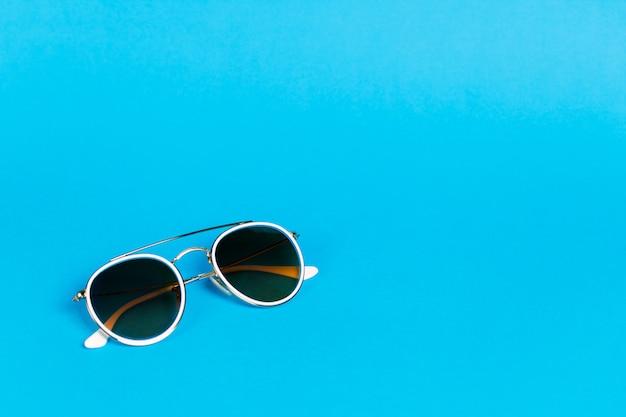 青に分離された白いフレームのサングラス。 Premium写真