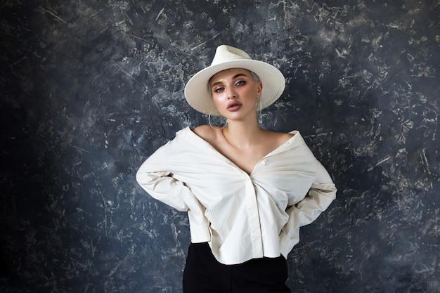 Красивая блондинка в белой рубашке и черных брюках Premium Фотографии